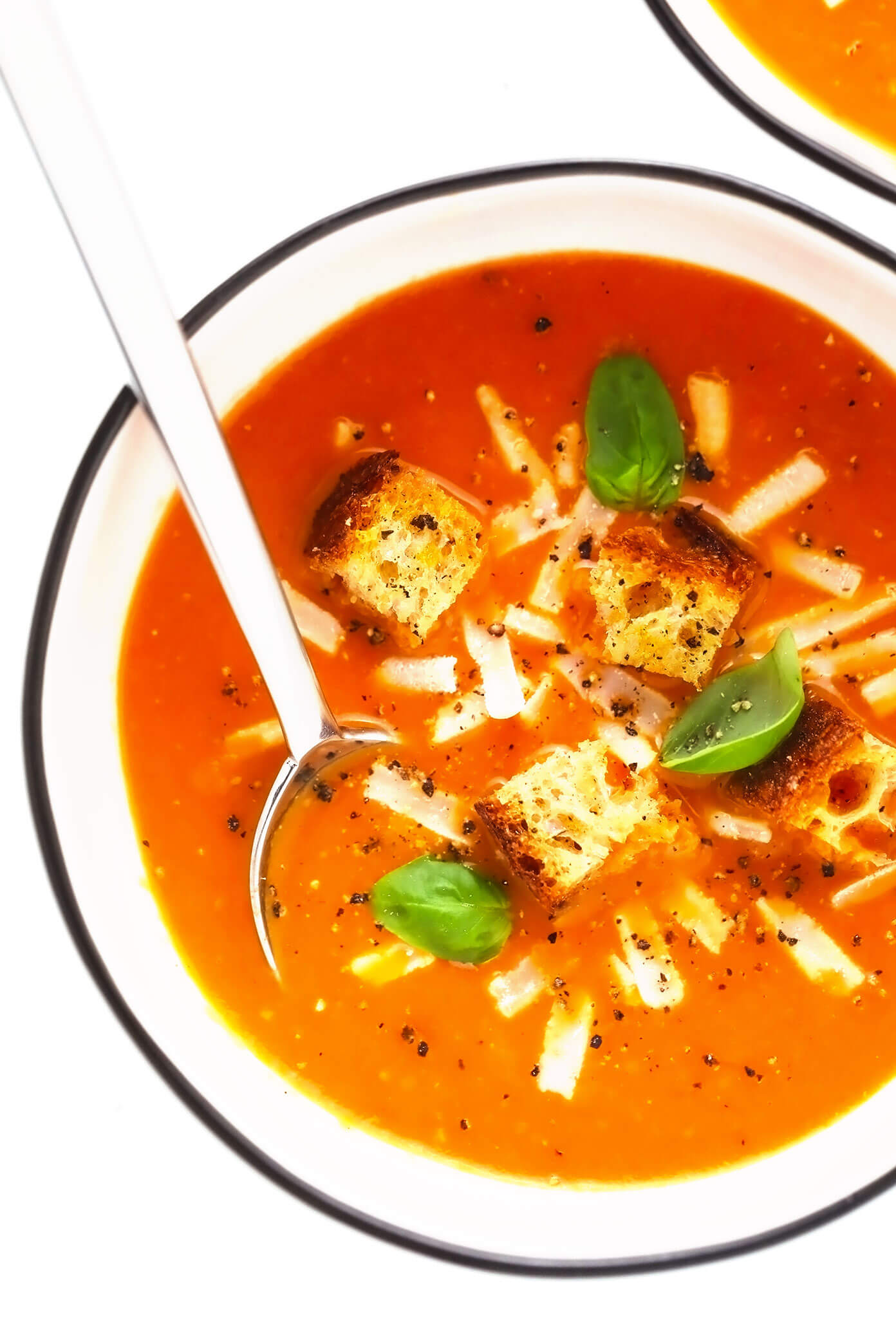 Roasted tomato soup in bowls with Parmesan, croutons and basil