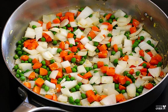 Saute onions, carrots and peas