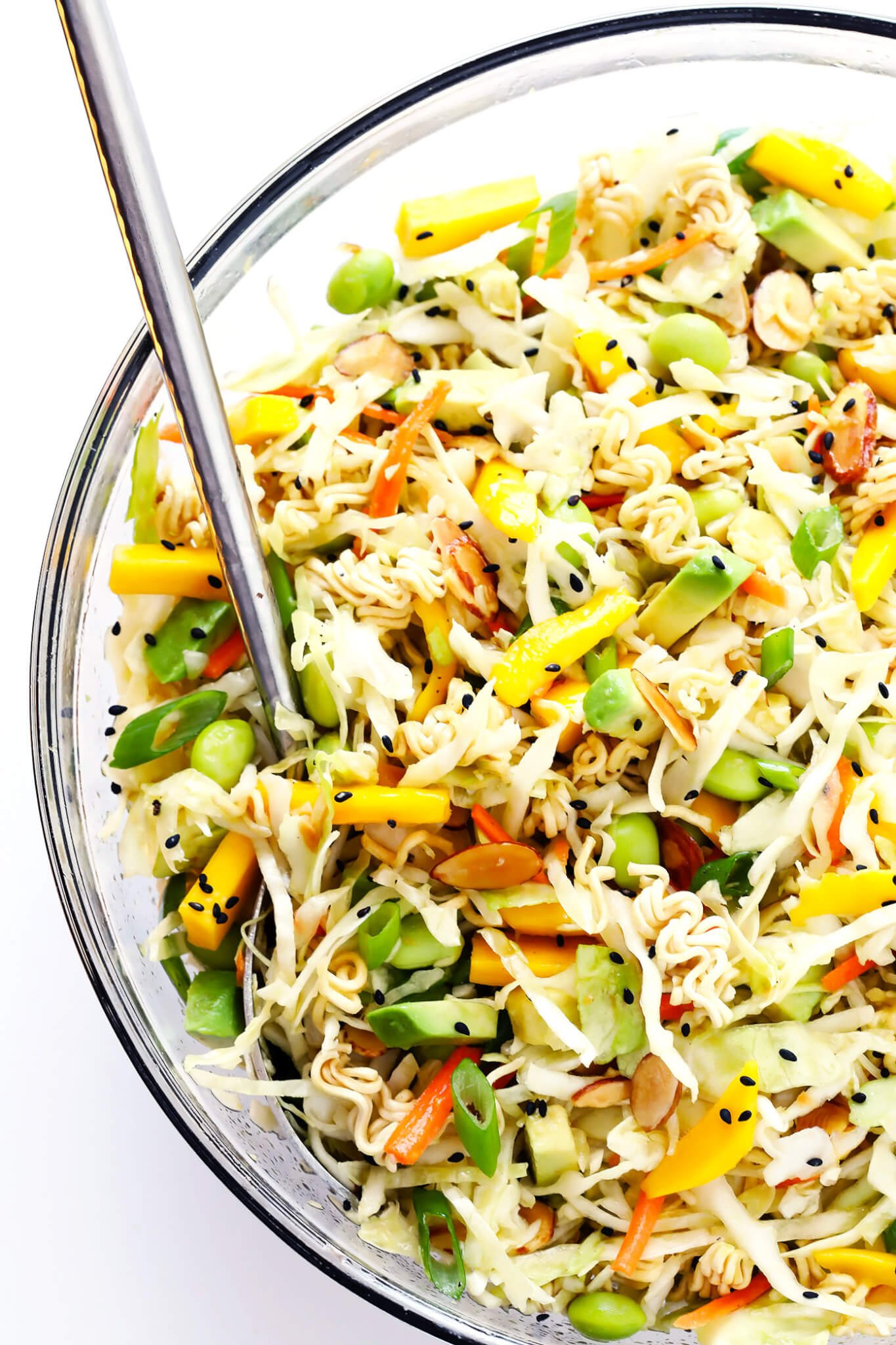 This Crunchy Asian Ramen Noodle Salad is easy to make, tossed with fresh mango, avocado, edamame, cole slaw, almonds, and a sesame honey vinaigrette...and SO delicious! Perfect for potlucks, picnics, or as a simple salad or side dish. | gimmesomeoven.com