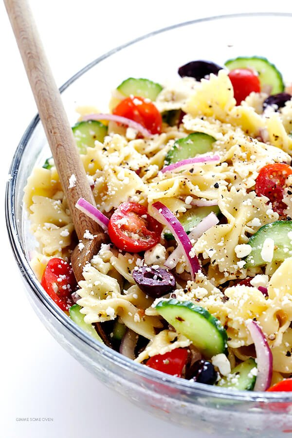 This Mediterranean Pasta Salad is SO GOOD! Love all of those cucumbers, tomatoes, Kalamata olives, red onions, and feta cheese. Perfect for a potluck! | gimmesomeoven.com
