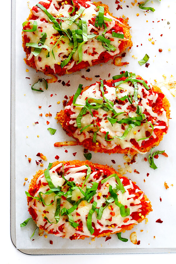 This Spicy Baked Chicken Parmesan recipe is made with a crispy seasoned panko crust, and topped with a spicy marinara sauce, melted mozzarella, and lots of fresh basil. It's surprisingly simple to make, and SO delicious!   gimmesomeoven.com