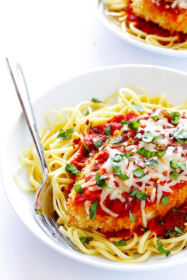 This Spicy Baked Chicken Parmesan recipe is made with a crispy seasoned panko crust, and topped with a spicy marinara sauce, melted mozzarella, and lots of fresh basil. It's surprisingly simple to make, and SO delicious! | gimmesomeoven.com