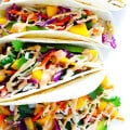 This Mango Chipotle Fish Tacos recipe is made with flaky mild fish, filled with a zesty mango slaw, and drizzled with a creamy chipotle lime sauce. So easy to make, and ready to go in less than 30 minutes! | gimmesomeoven.com