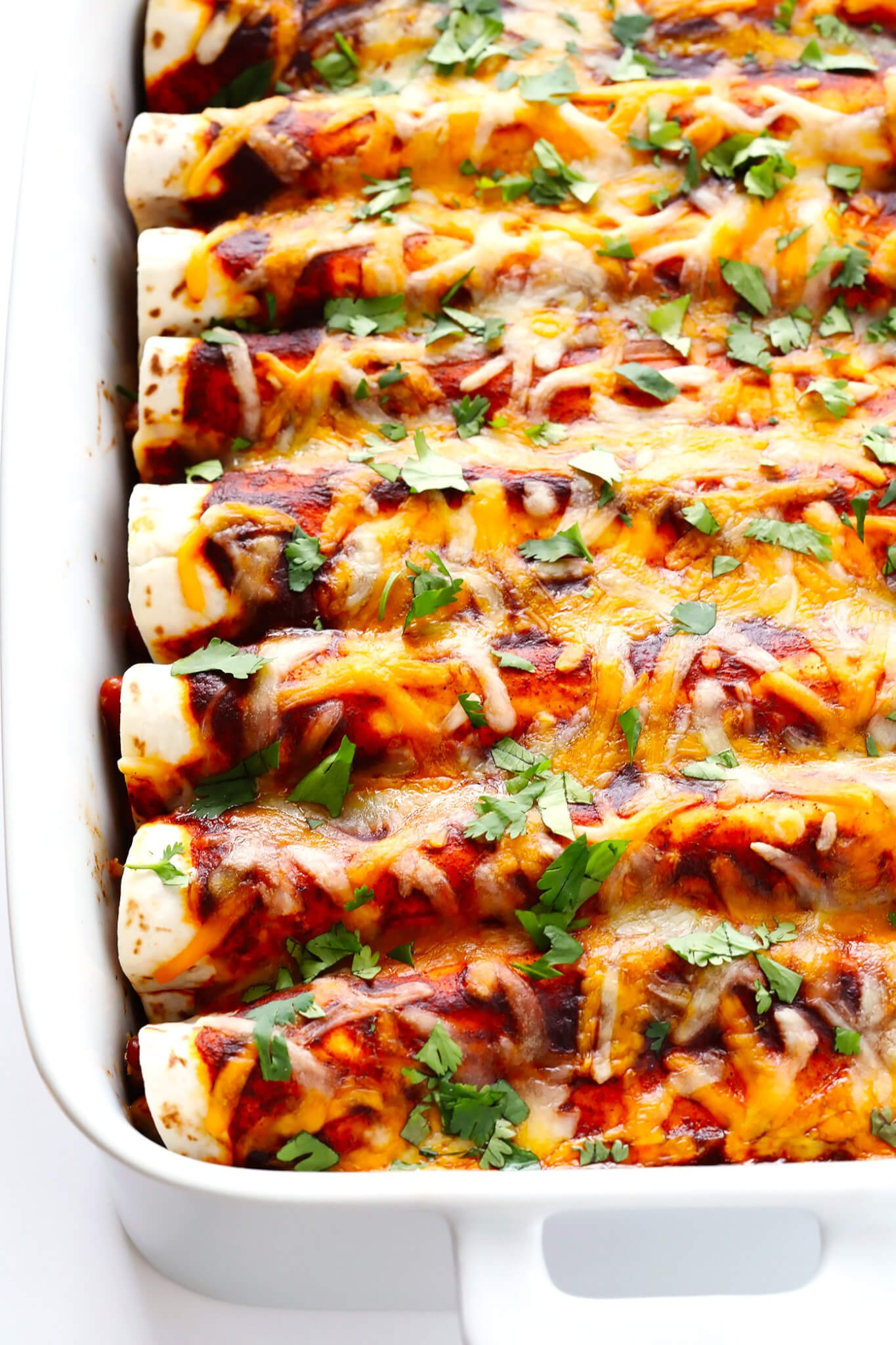 This Ancho Chicken Enchiladas recipe is easy to make, full of big flavor, nice and cheesy and filled with chicken and beans, and perfect for Cinco de Mayo or anytime you're feeling like Mexican food! | gimmesomeoven.com