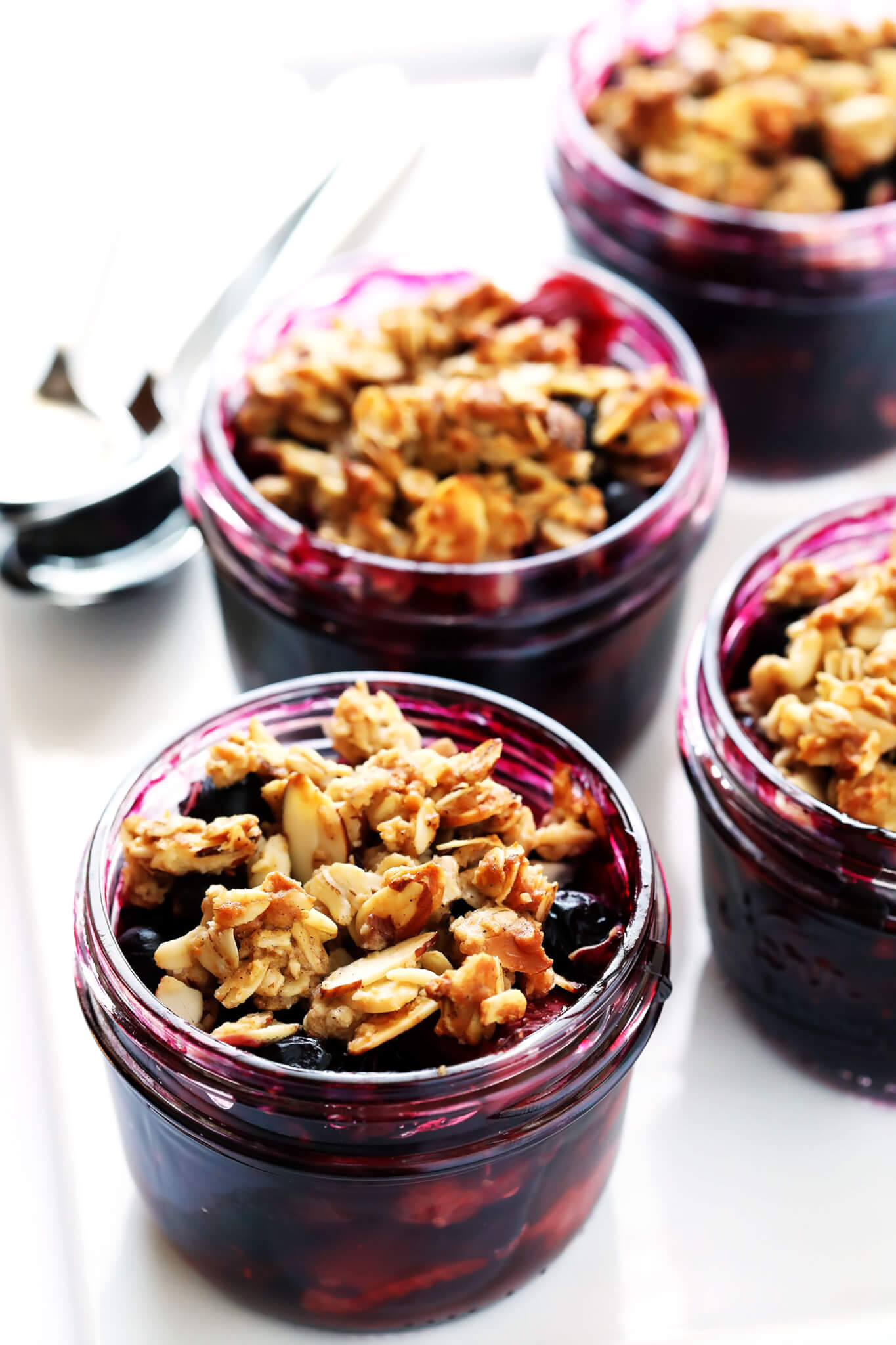 These Mini Mason Jar Fruit Crisps are easy to make with blueberries or your favorite fruit, and topped with a yummy oatmeal-almond topping. They're the perfect quick and easy and seasonal dessert! | gimmesomeoven.com