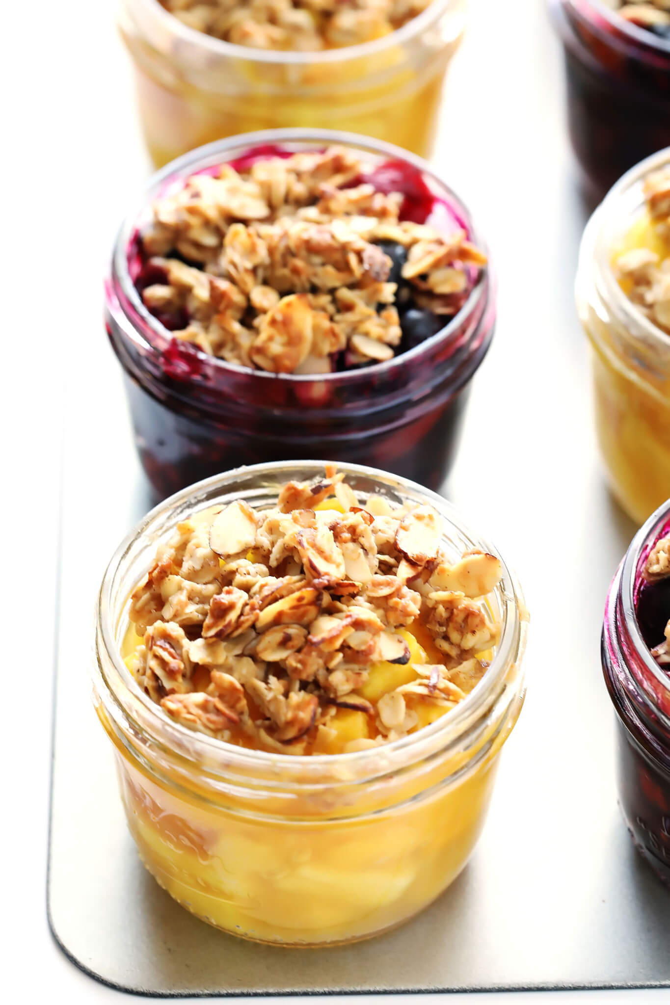 This Mini Mason Jar Fruit Crisps recipe can be made with your favorite seasonal fruit, they're topped with a delicious oatmeal-almond crumble, and they are SO delicious! Feel free to make them with blueberries, strawberries, cherries, peaches, pineapple, apples, pears...you name it! They're one of my favorite easy dessert recipes. | gimmesomeoven.com (Gluten-Free / Vegetarian)