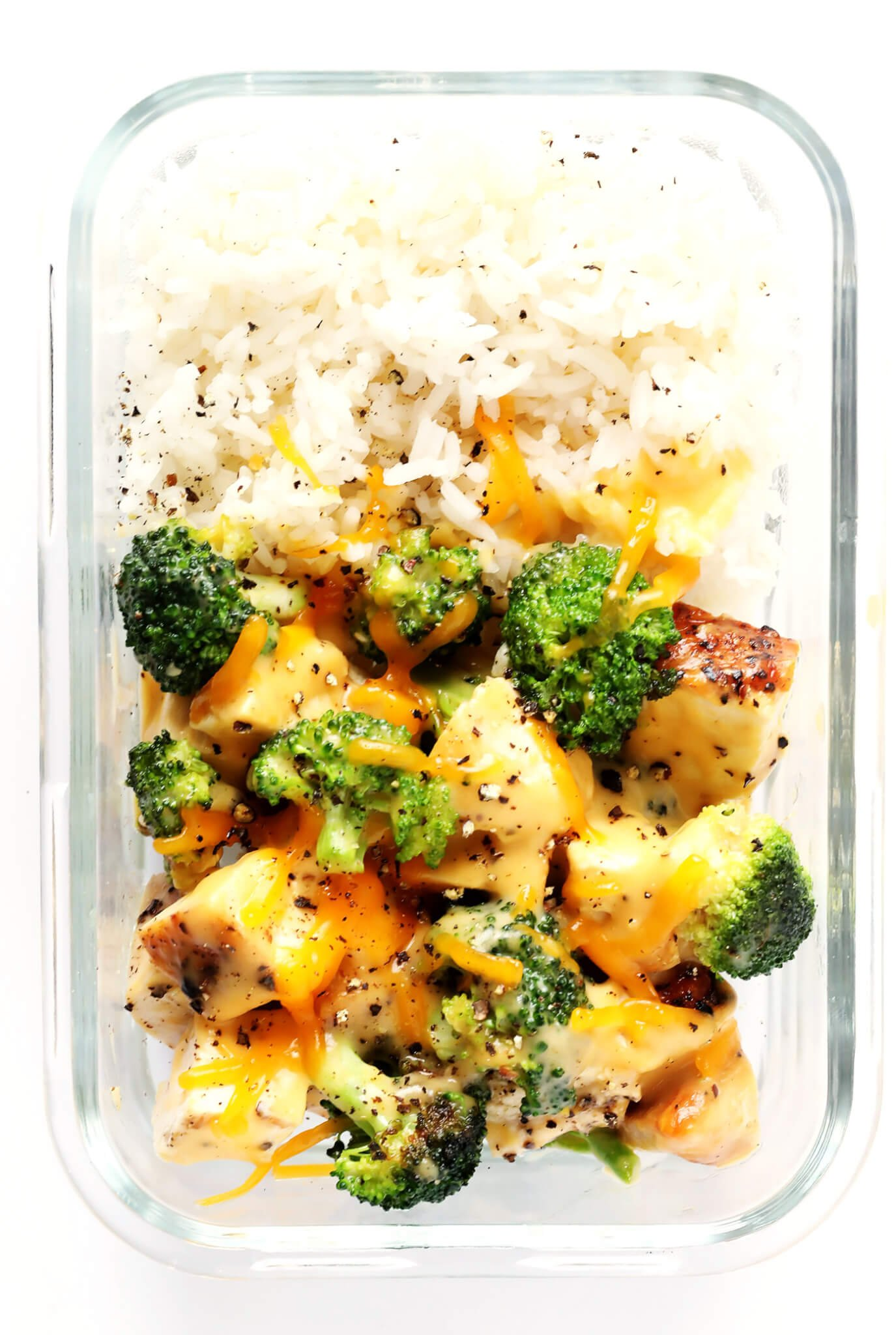 These Cheesy Broccoli, Chicken and Rice Bowls are perfect for easy meal prep or weeknight dinner, they're tossed with a lightened-up garlicky cheddar cheese sauce, and they're totally savory and delicious! Feel free to serve with rice or quinoa. | gimmesomeoven.com