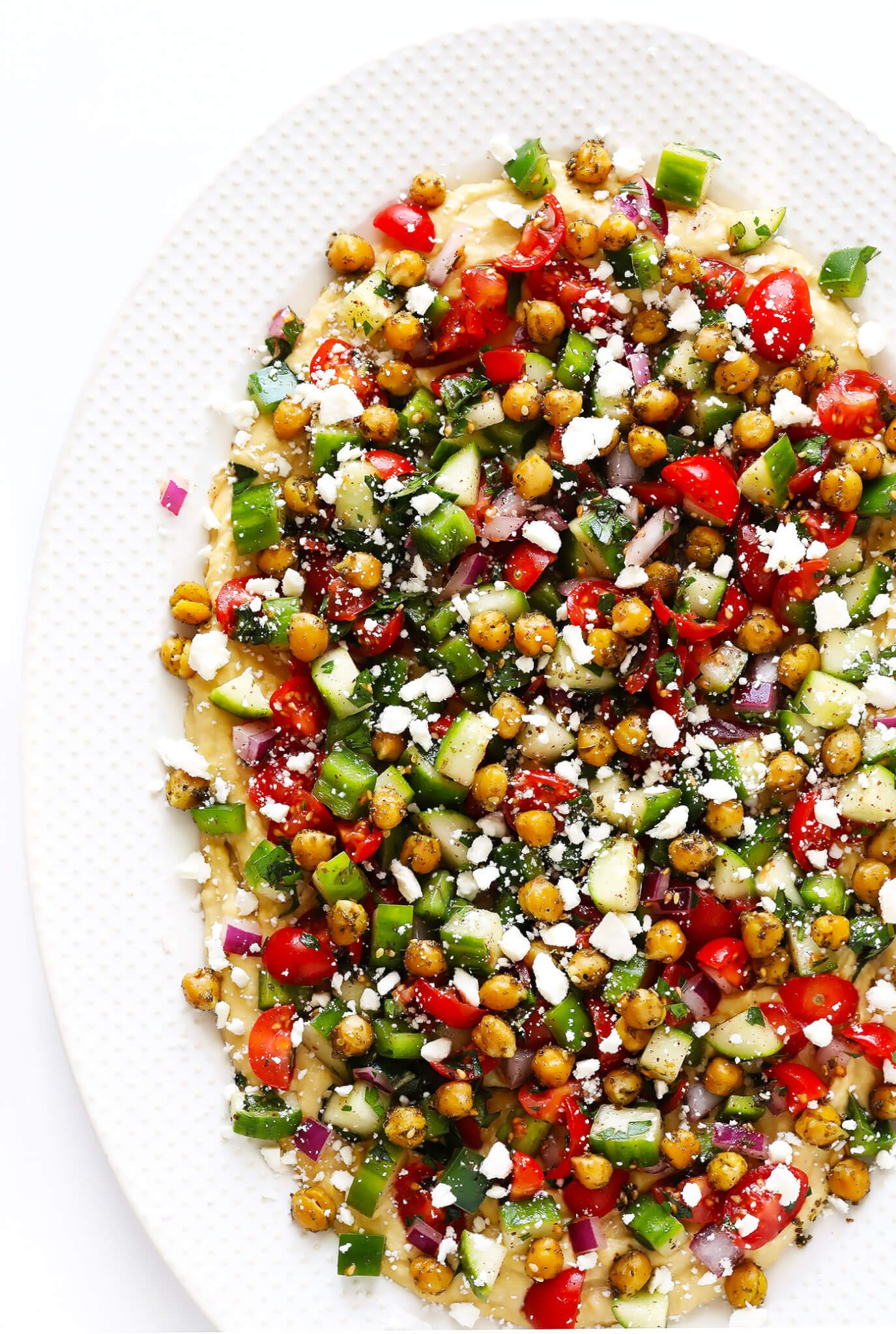 This delicious Israeli Salad recipe is quick and easy to make, full of the fresh flavors of tomatoes, cucumbers, peppers, mint, parsley and sumac, and it's so delicious! Serve it up on its own, or use it to make a simple pita wrap or hummus dip! | gimmesomeoven.com