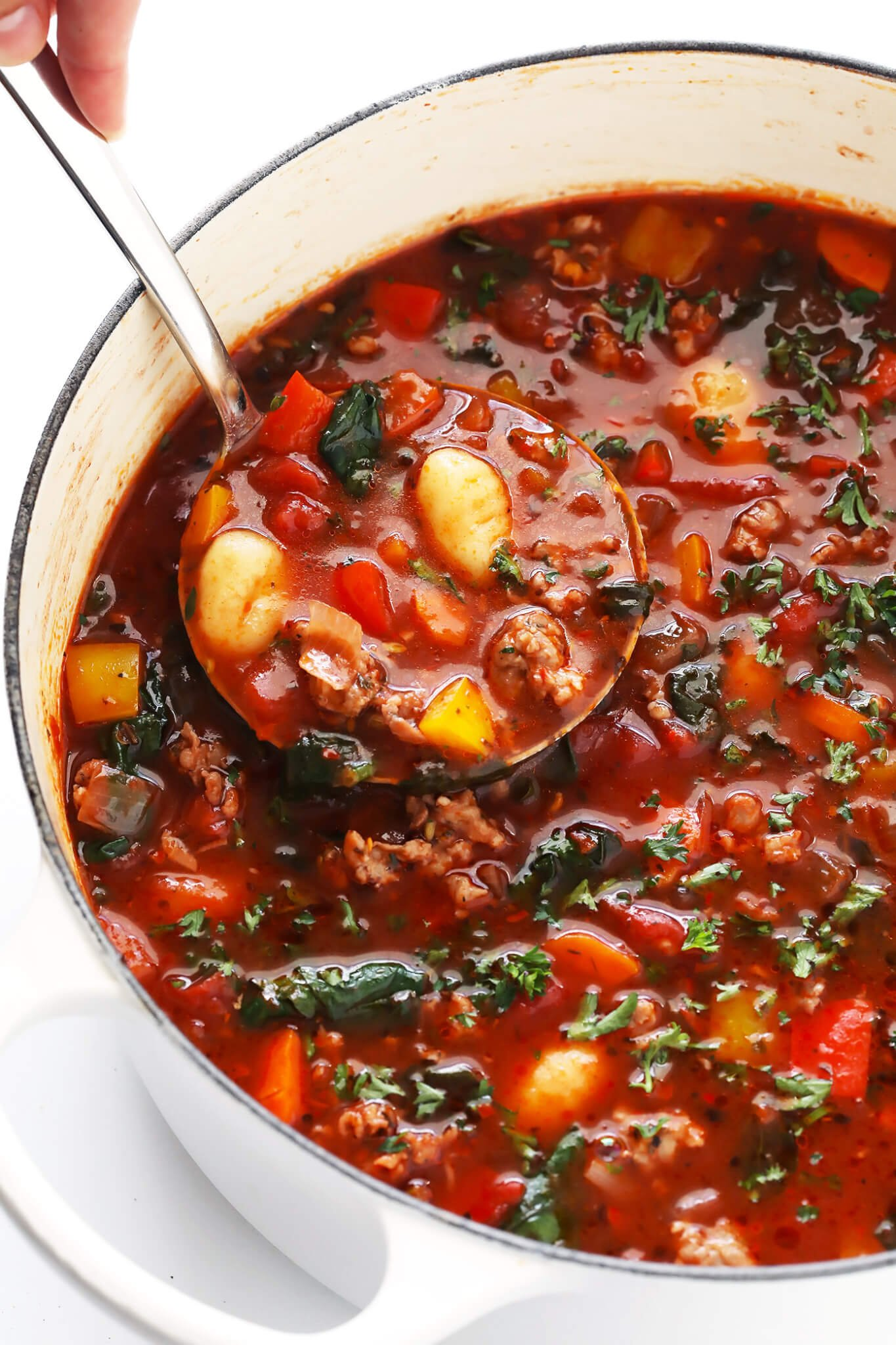 This Italian Sausage, Gnocchi and Tomato Soup recipe is SO cozy and delicious! It's filled with your choice of sausage (pork, chicken, turkey, or vegan), lots of veggies (bell peppers, onions, carrots, celery), lots of tomatoes, tender gnocchi (or diced potatoes), and topped with lots of Parmesan and fresh herbs. Oh, and it's also naturally gluten-free! My kind of comfort food! | gimmesomeoven.com