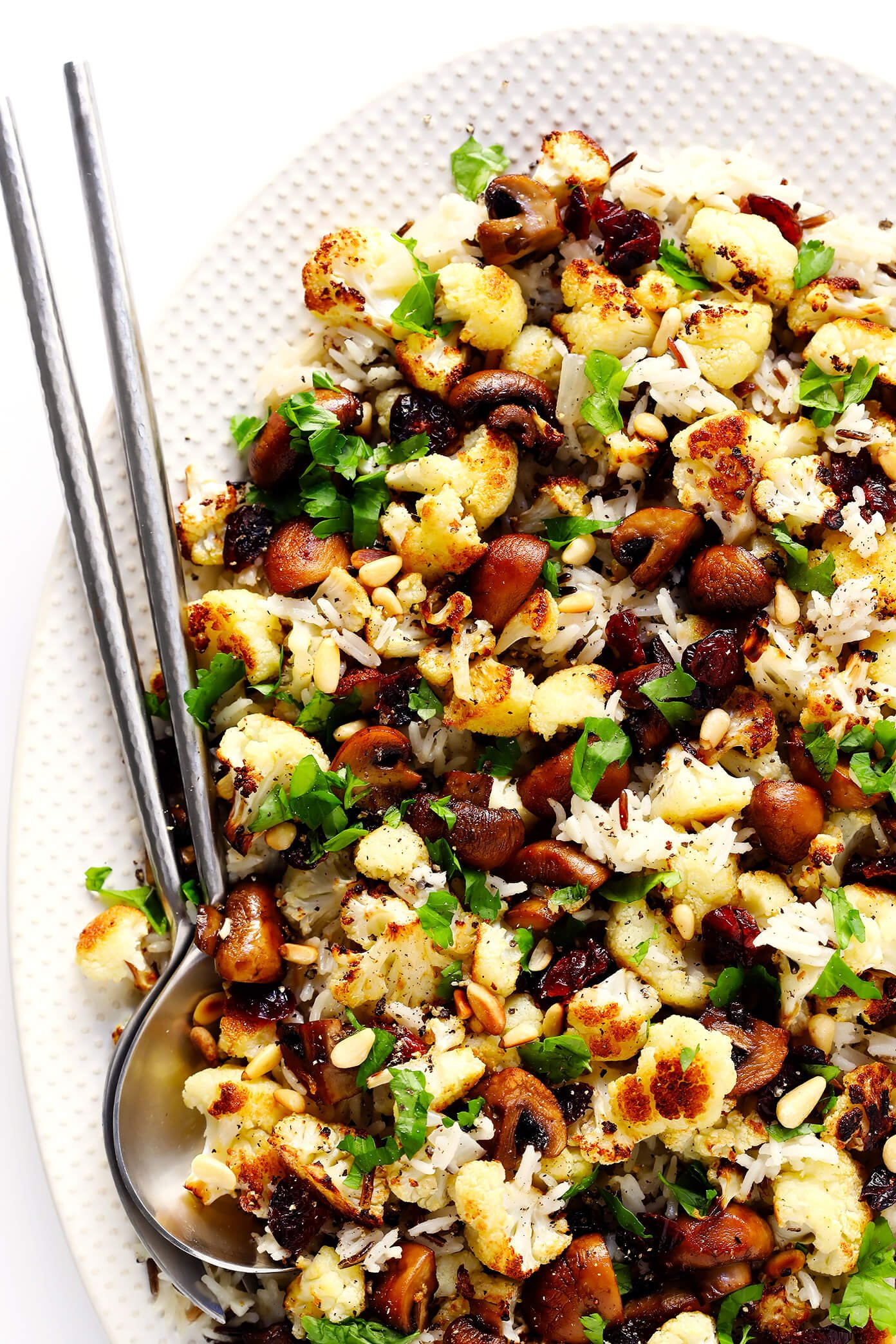 "This Roasted Cauliflower, Mushroom and Wild Rice ""Stuffing"" is the perfect recipe to serve as a Thanksgiving side dish...or as dinner any night of the year! It's naturally gluten-free, vegetarian and vegan. It's made with delicious lemon-garlic rice, dried cranberries, toasted pine nuts, and roasted veggies. And it's AWESOME."