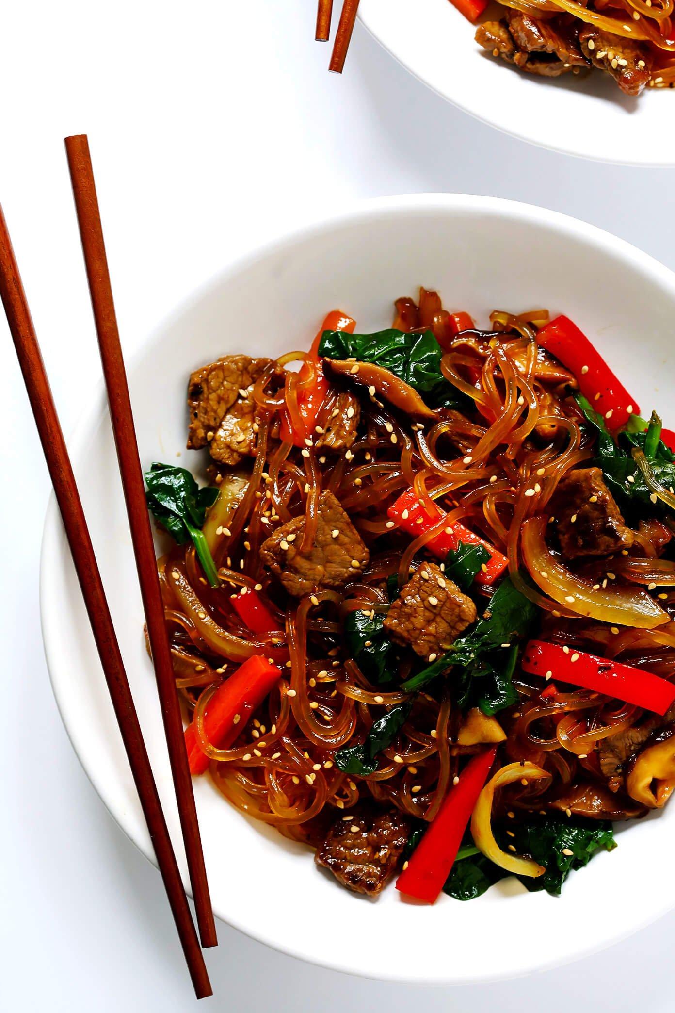 Japchae - Korean beef noodle stir-fry in bowl with chopsticks