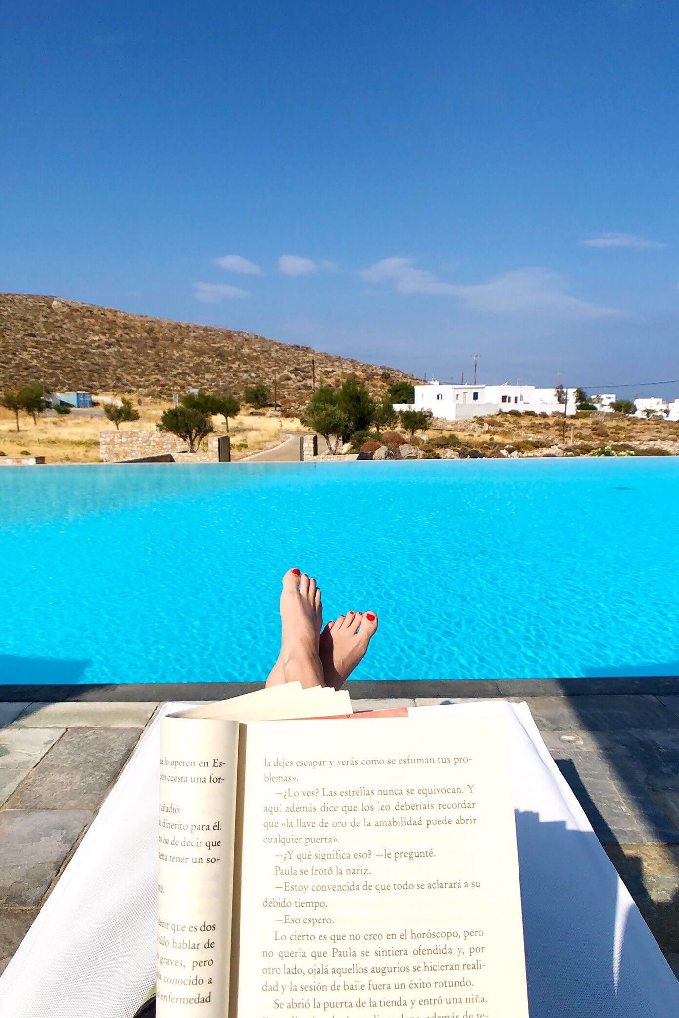 Reading by the pool at Anemi Hotel in Folegandros, Greece
