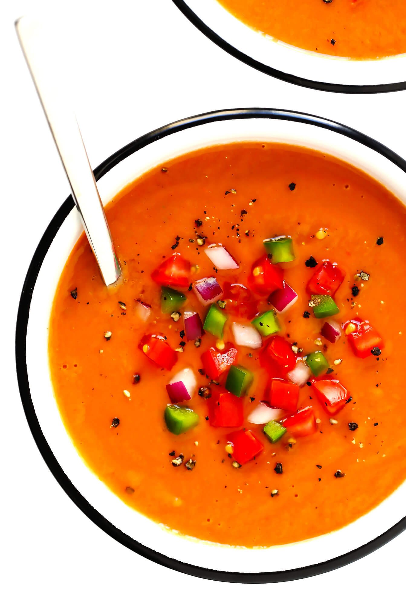 Bowl of Spanish gazpacho, topped with tomato, green pepper and red onion
