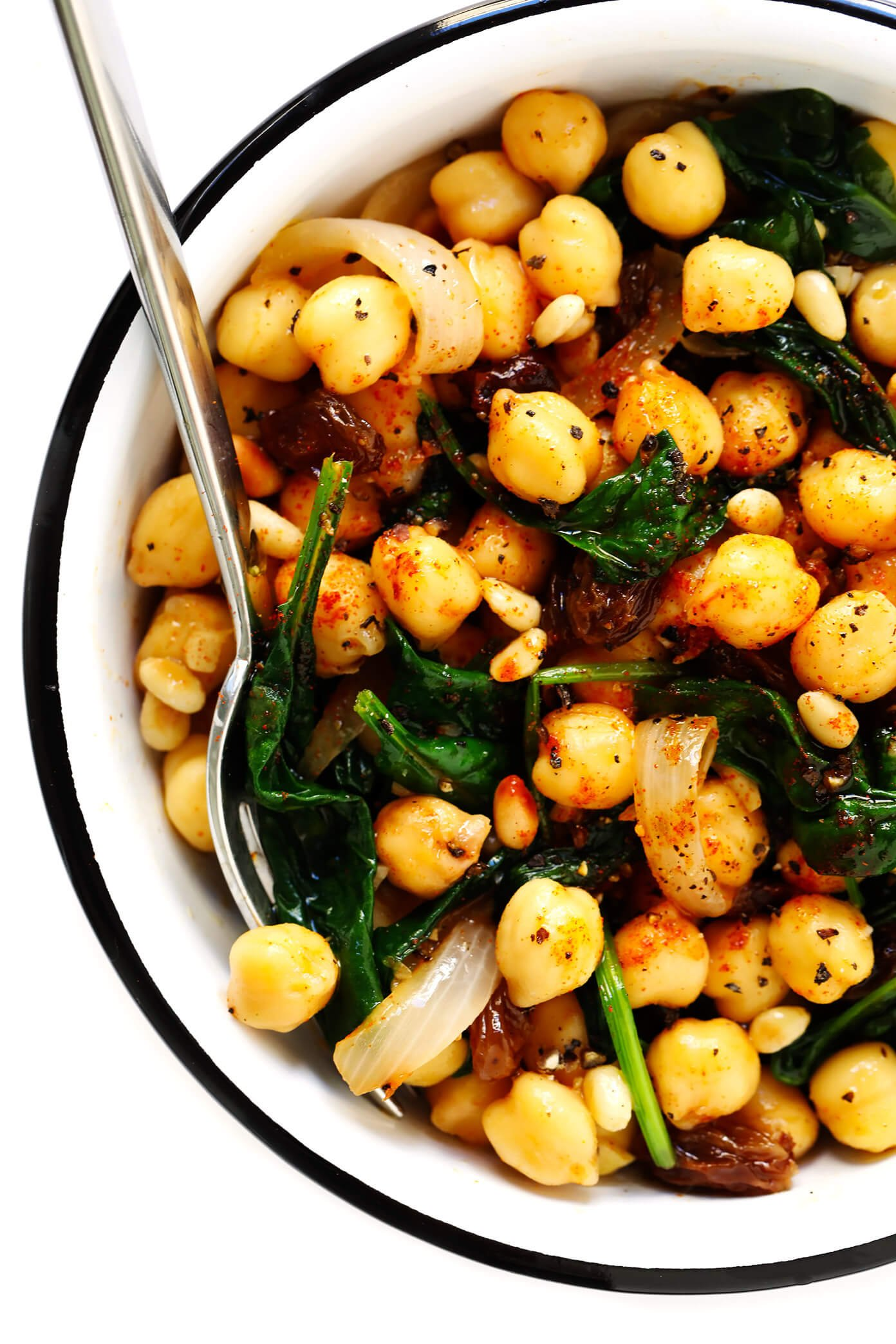 Spinach chickpeas and onions in a white bowl