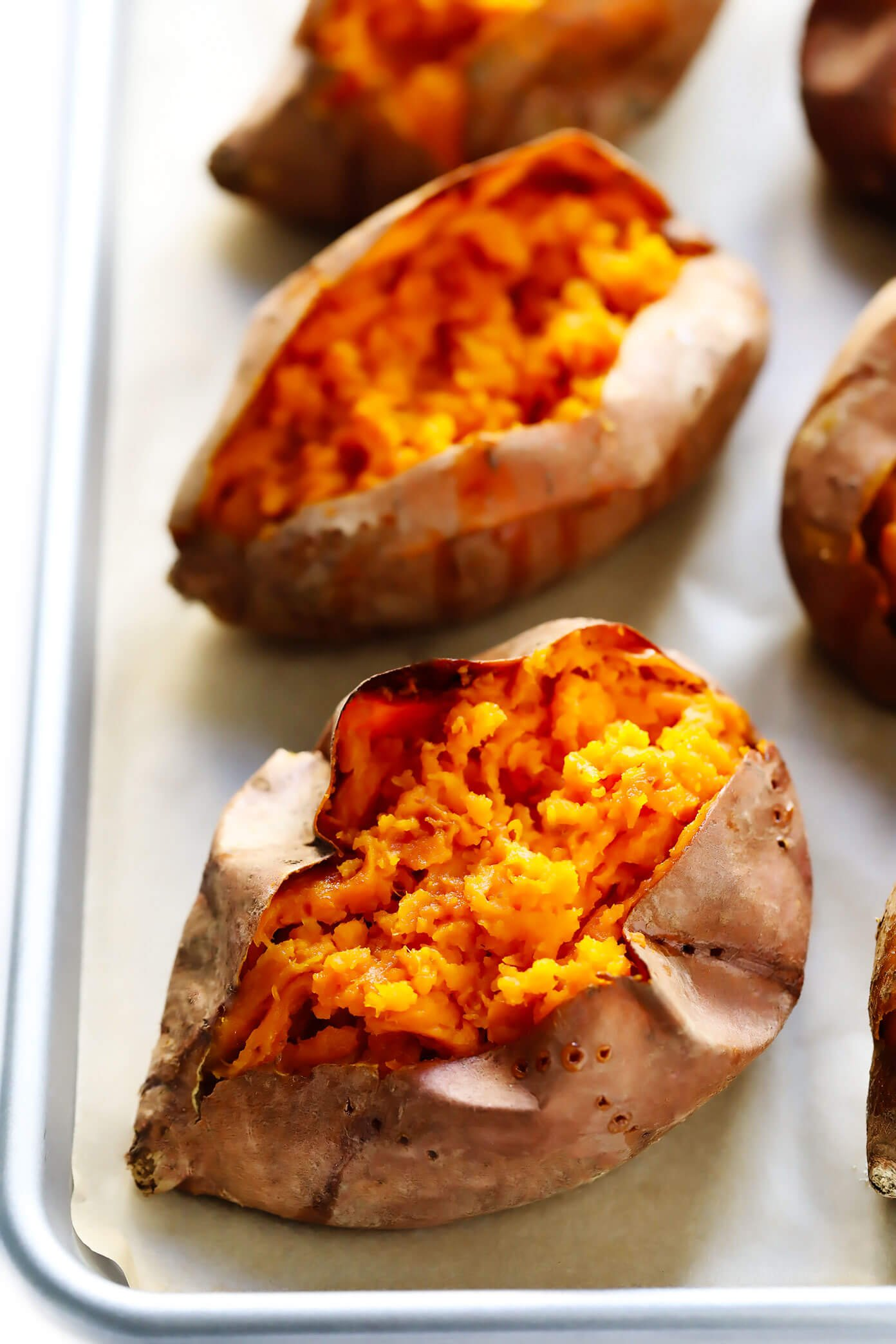 Plain baked sweet potatoes on a baking sheet