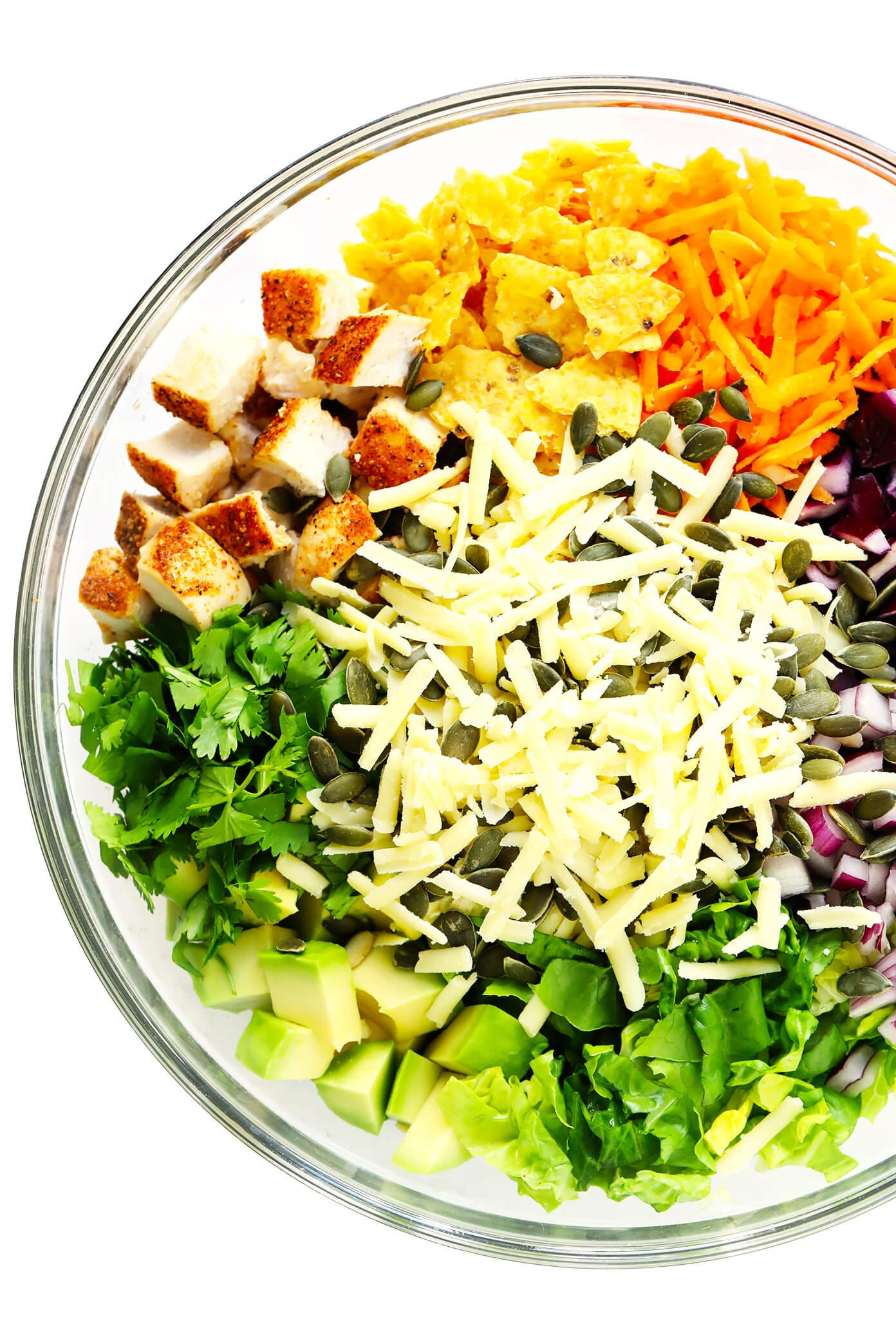 Bowl of Ingredients for Chipotle Chopped Salad -- Chicken, Tortilla Chips, Carrots, Cabbage, Red Onion, Romaine Lettuce, Cilantro, Baked Chicken, Cheddar Cheese and Pepitas