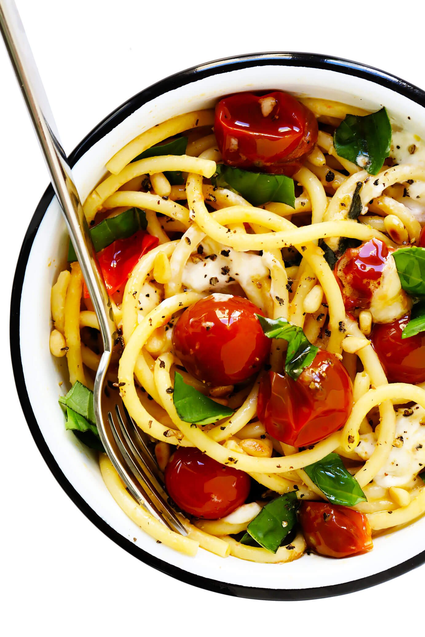 Serving bowl of pasta with cherry tomatoes, burrata and basil