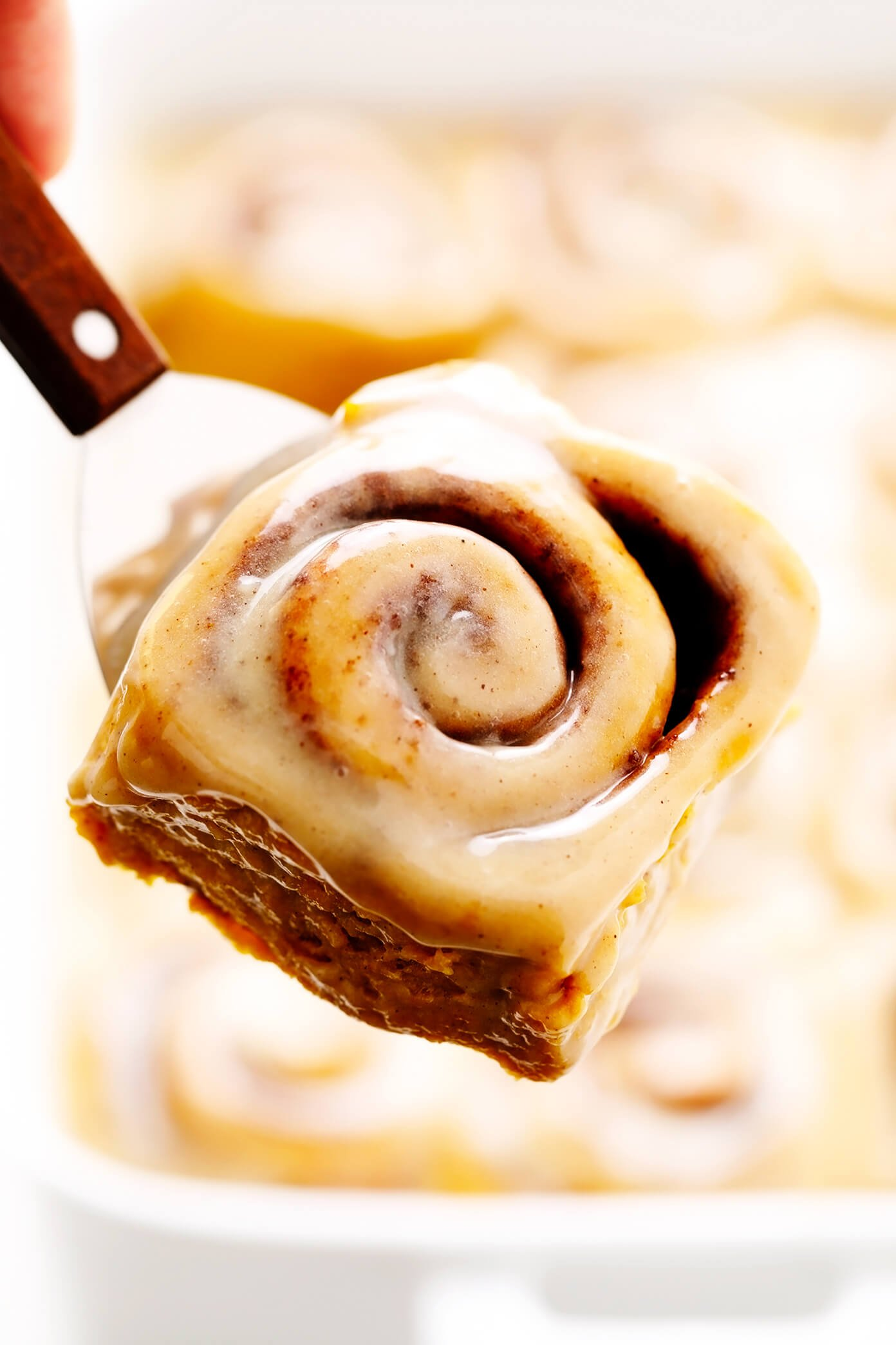 Pumpkin Cinnamon Rolls lifting out of pan Favorite Family Recipes