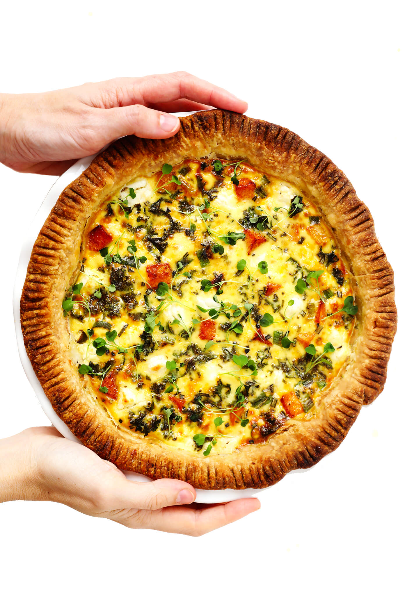 Holding a whole pan of Butternut Squash, Kale and Goat Cheese Quiche