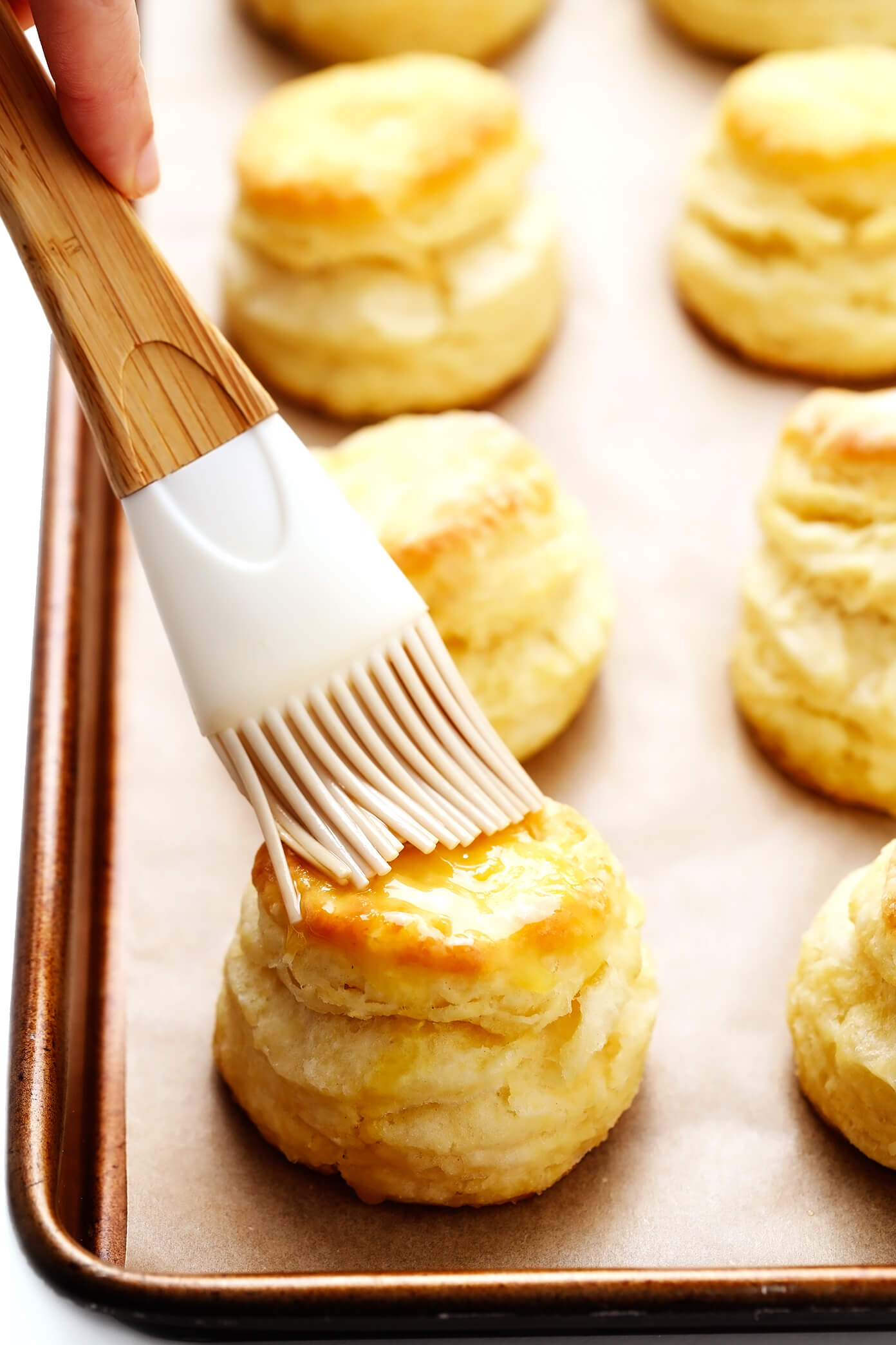 Brushing butter on homemade biscuits