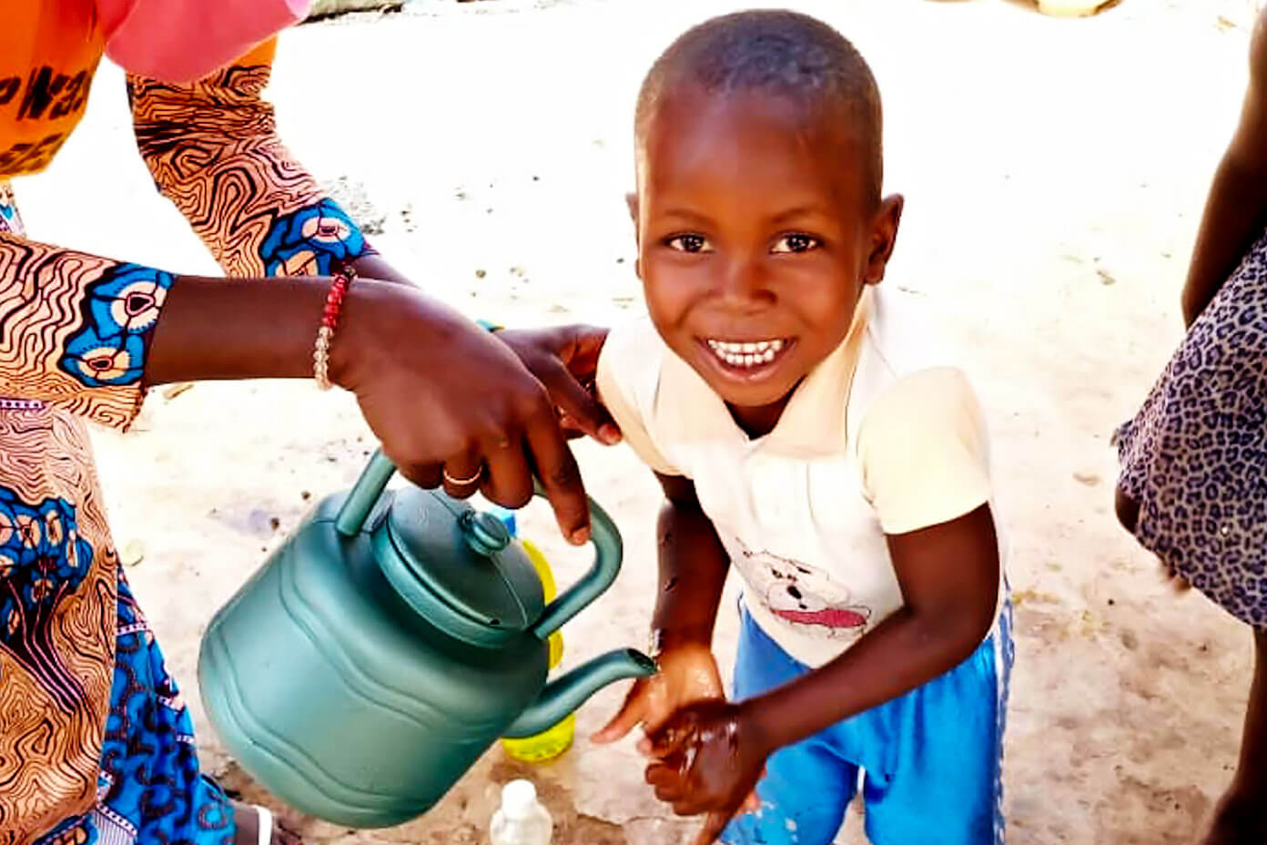Young boy in Mali washing his hands with soap and clean water