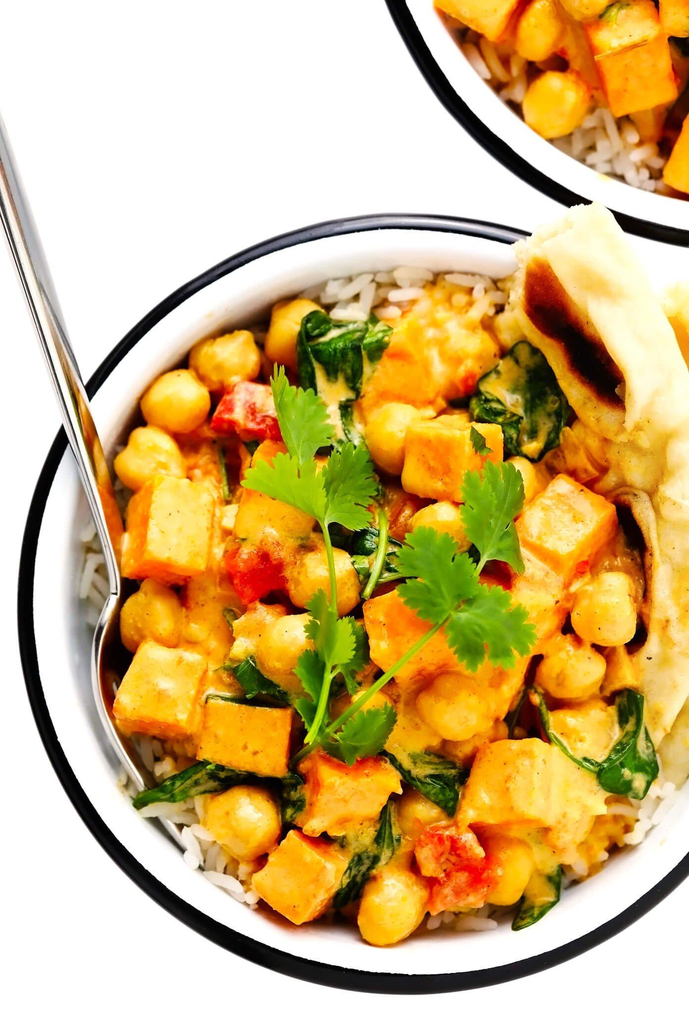 Batata doce grão de bico e coco curry em uma tigela com pão naan e arroz