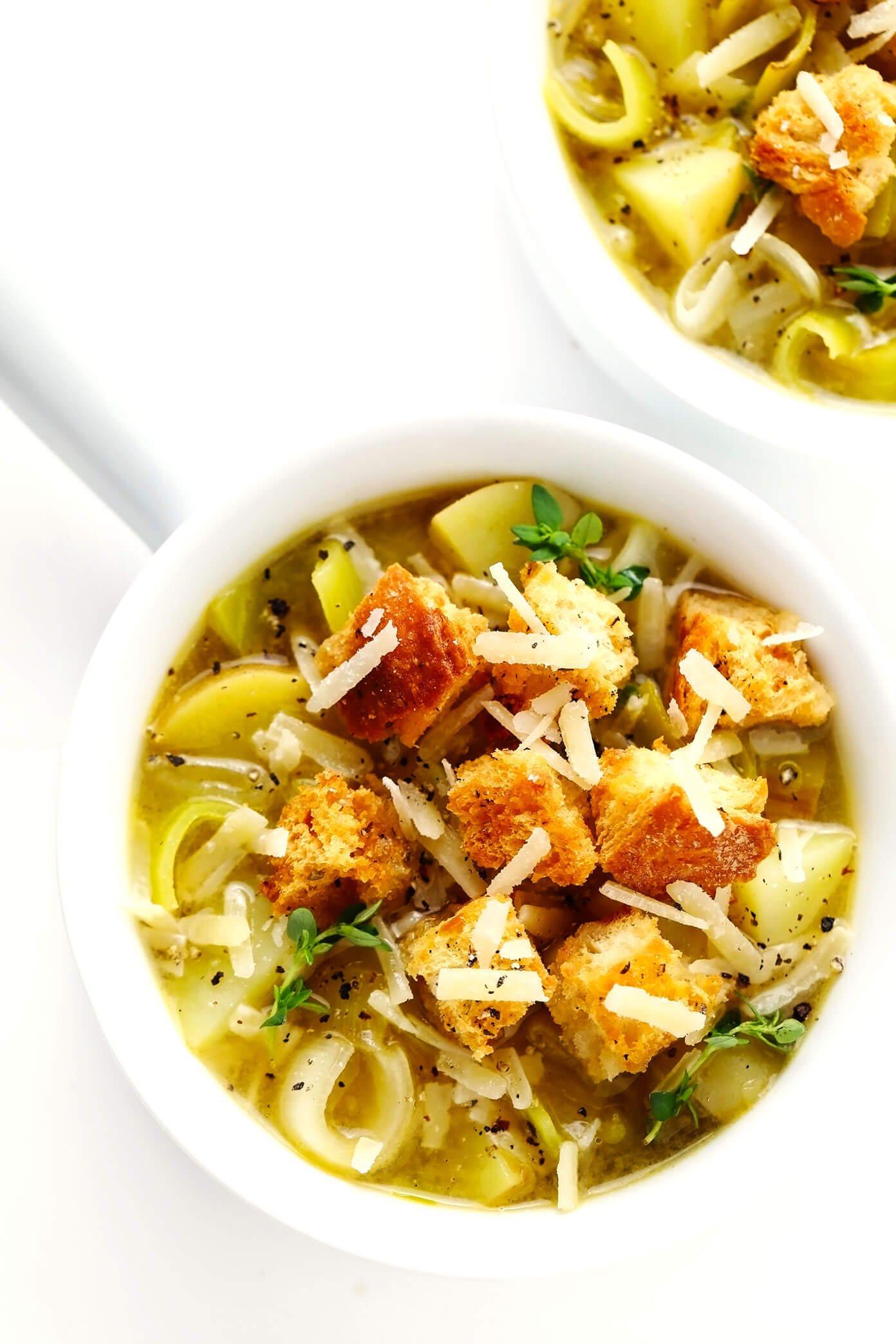 Tigelas de sopa rústica de batata com alho-poró e pão caseiro com queijo parmesão