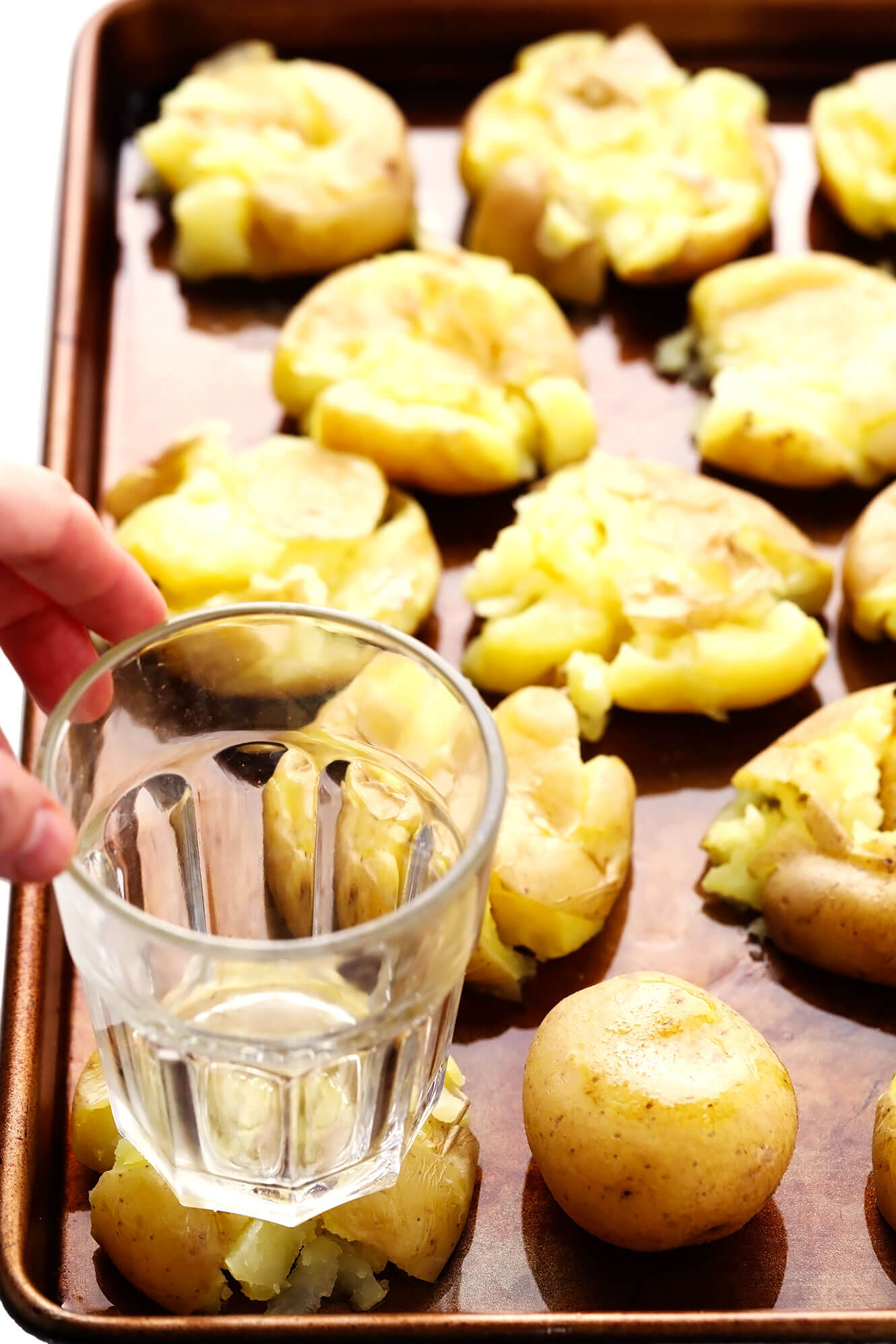 Smashing boiled potatoes with a drinking glass