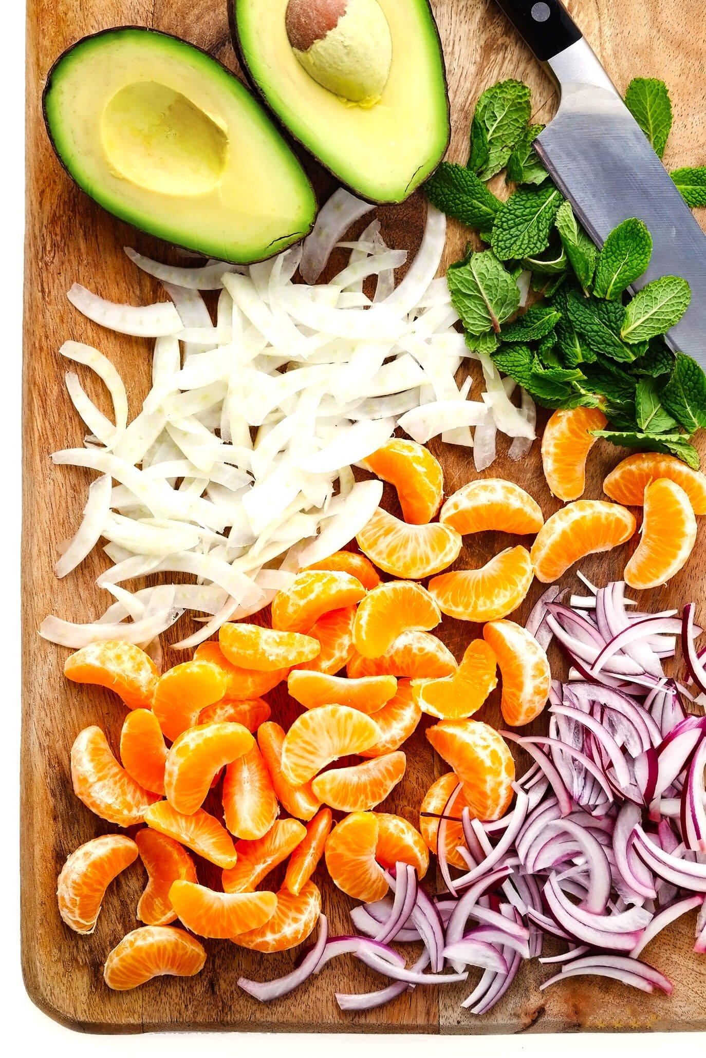 Tábua de cortar com abacate fresco, erva-doce, cebola roxa, hortelã e laranjas clementina