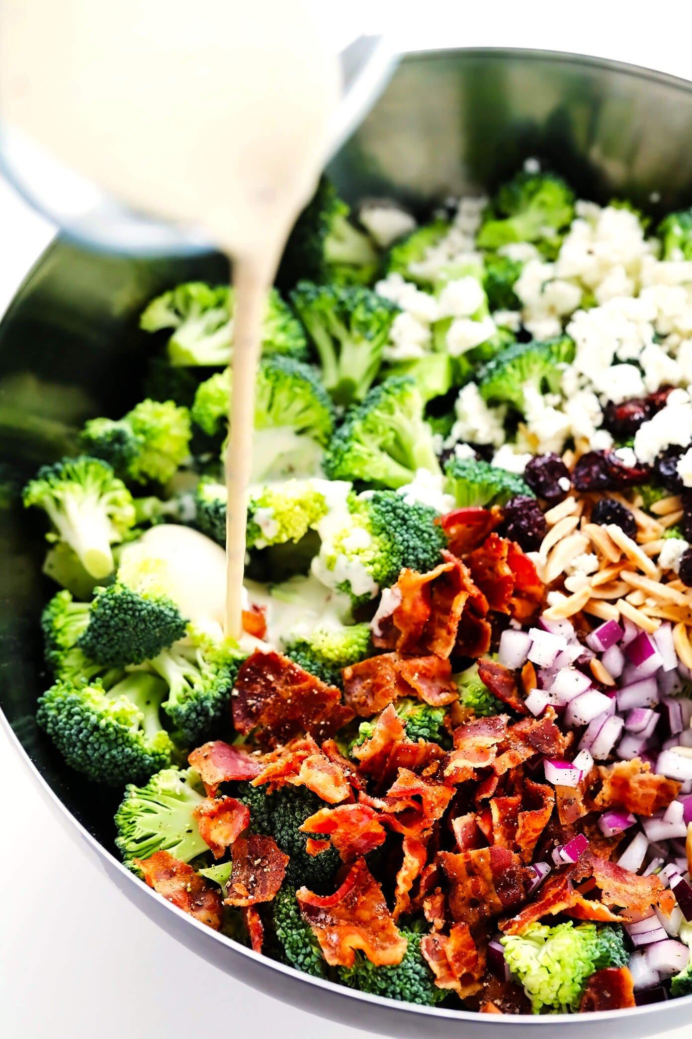 Pouring creamy dressing into broccoli salad