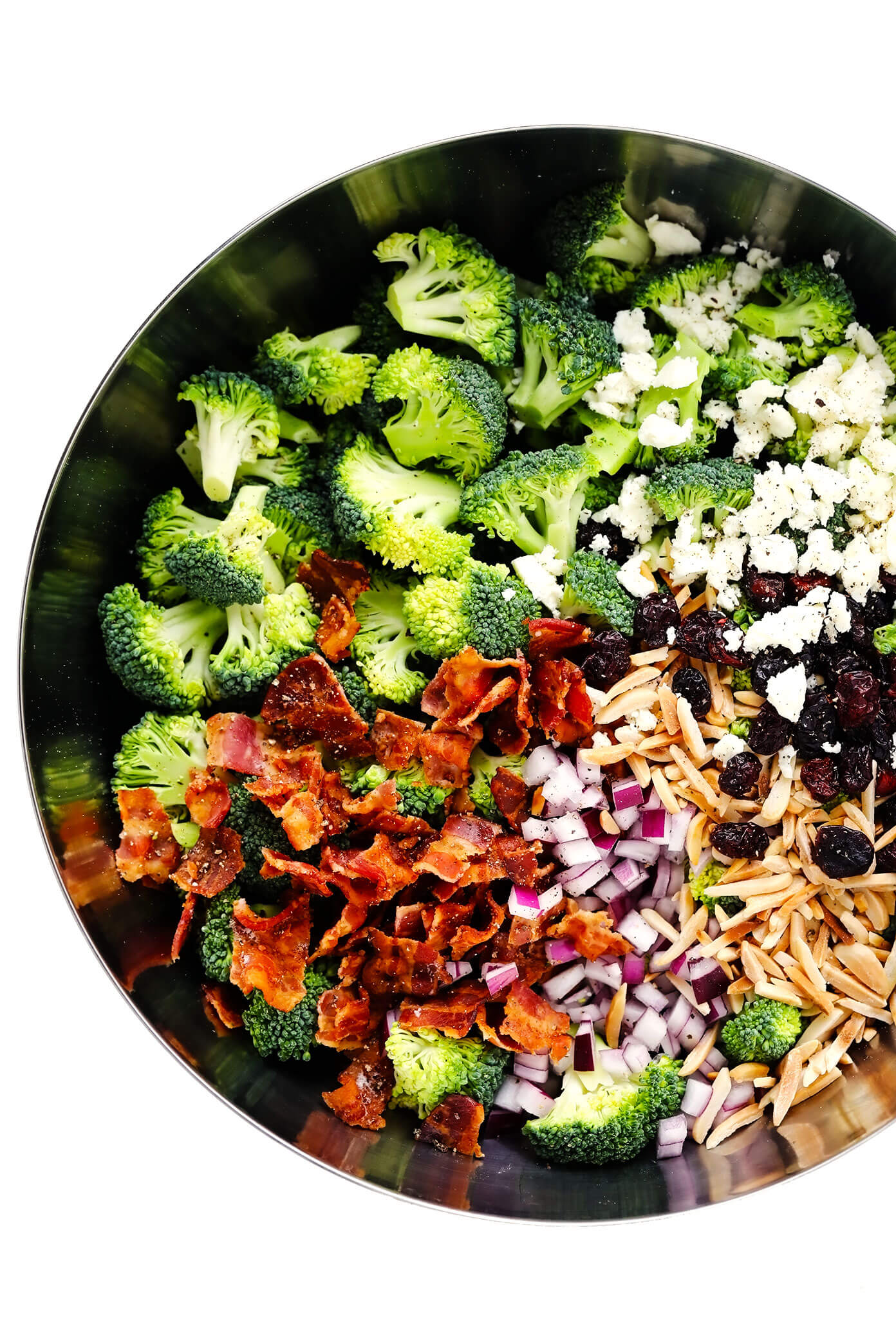 Broccoli Salad Ingredients In Bowl - Broccoli Florets, Bacon, Red Onion, Toasted Almonds, Dried Cranberries and Feta Cheese