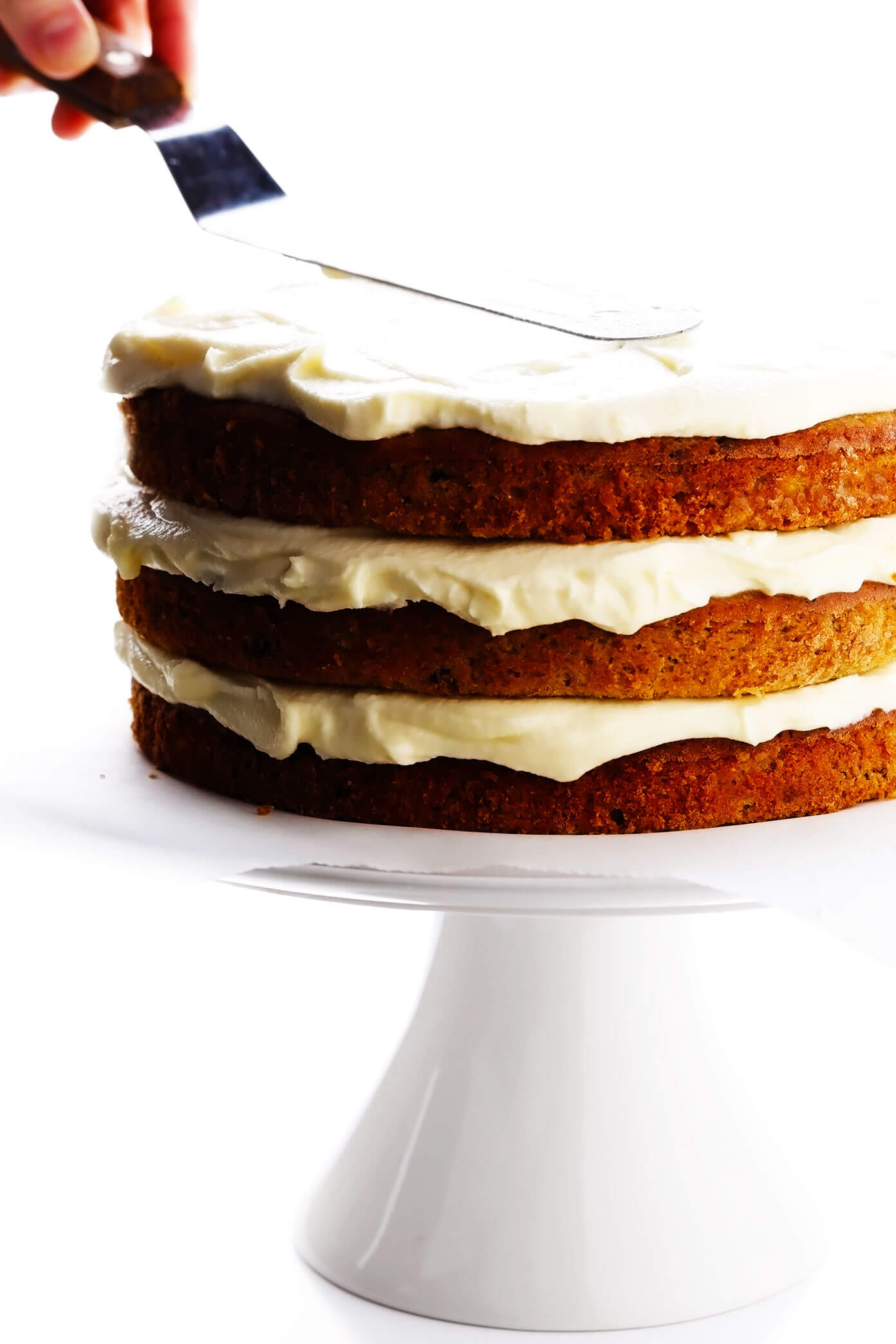 Assembling hummingbird cake layers with cream cheese frosting
